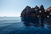Tourist boat in front of the fascinating, rugged volcanic rock in the Scandola nature reserve, Galeria, Corsica, France
