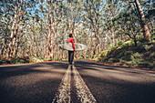 Surfer stands in the Boranup Forest in Margaret River, Western Australia, Australia, Oceania