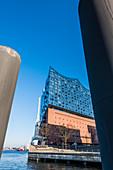 Die Elbphilharmonie, eingerahmt von zwei riesigen Pollern, Hafencity, Hamburg, Deutschland