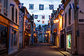 Rue Dumont d'Urville with blue and white flags at dusk, Concarneau, Arrondissement Quimper, Departement Finistere, Brittany, France, Europe