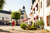 Man walks across the Place du Bouffay, in the background the town hall of La Roche-Bernard, Vilaine, Morbihan department, Brittany, France, Europe