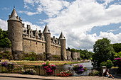 Josselin Castle with the Oust River and colorful flowers in summer, Josselin, Dept. Morbihan, Brittany, France, Europe