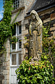 Stone statue of a praying woman in robe in the castle park, Rochefort en Terre, Morbihan department, Brittany, France, Europe