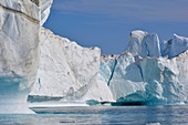 Disco bay; West Greenland; Icebergs in the Kangia Icefjord near Ilulissat; diverse ice formations; Steep walls at the foot hollowed out by the water; Cracks light turquoise; strange ice towers; blue sky; calm water surface; Seagulls fly between the icebergs