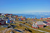 Disco bay; West Greenland; brightly painted wooden houses by Ilulissat; View of the Disko Bay; floating ice floes; mountainous terrain; Mountain range in the background; blue sky and sunshine