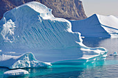 Icebergs off Uummannaq in West Greenland; diverse surfaces and structures; Ice under water glows intensely turquoise; steep, rocky mountain wall in the background; cloudless sky and absolutely calm water surface