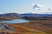 Landscape near Kangerlussuaq, West Greenland; small lake framed by hills; autumnal tundra vegetation; Leaves of the low plants have turned yellow and red; Mountains in the background; nice weather