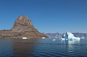 "Iceberg in front of Uummannaq; Island in West Greenland; ""uummannaq"" means the ""seal-shaped"" and refers to the shape of the mountain; below the mountain are the colorful wooden houses in the hills; an iceberg and numerous ice floes float off the island;"