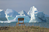 Disco island; Icebergs off the coast at Qeqertarsuaq; West Greenland; there is a chair on the bank; invites you to look at the landscape and linger
