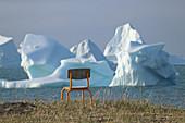 Stuhl am Ufer, Diskoinsel, Eisberge vor der Küste bei Qeqertarsuaq, Westgrönland, Grönland