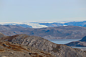 Mountain landscape with lake near Kangerlussuaq; West Greenland; autumnal tundra vegetation; rocky hilly landscape; View of the inland ice and a glacier tongue;