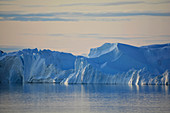 Disco bay; West Greenland; Icebergs in the Kangia Icefjord near Ilulissat; Mountain landscape made of ice; Morning sun colors the sky light orange; Streaks of clouds run across the sky; Icebergs shimmer in many different shades of blue