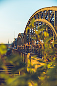 People sit at sunset on the Hackerbruecke in Muenchen, Bavaria, Germany, Europe
