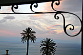 Sunset with palm trees and bars and sea, Taormina, east coast, Sicily, Italy