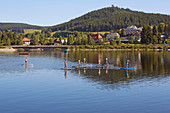 Stand up paddlers on summer morning at Schluchsee, Southern Black Forest, Black Forest, Baden-Wuerttemberg, Germany, Europe