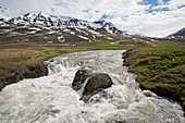 Fast flowing river with mountain backdrop\nIceland\nLA007106