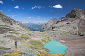Hikers on the turquoise Gradensee at the Nossberger Hütte in the Gradental in the Hohe Tauern National Park, Austria