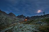 Dramatic clouds with illuminated Adolf Nossberger hut in the Gradental at night in the Hohe Tauern National Park, Austria