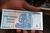 African man's hand holding a one hundred-trillion dollar note, Zimbabwe.