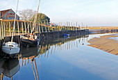 A view of the quayside and moorings at the west end of the harbour on the North Norfolk coast at Blakeney, Norfolk, England, United Kingdom.