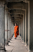 Siem Reap, Cambodia - January 19, 2011: A monk is wearing a orange robe and walking in the Angkor Wat complex.