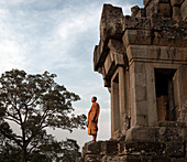 Siem Reap, Cambodia - January 19, 2011: A monk is standing on a platform in Ta Keo, which is part of Angkor.