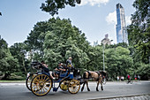 New York, United States of America - July 10, 2017. Asian tourists taking a tour on a horse-drawn carriage in Central Park.