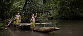 Papua New Guinea - November 8, 2010:  Father and son wearing traditional tribe clothing are rowing a boat in the jungle.