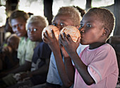 Papua New Guinea - November 12, 2010: Two boys are drinking water from a coconut.