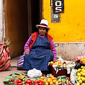 Cusco, Peru - Dezember 17, 2011: A woman wearing traditional clothing is selling a variety of vegetables and fruits on the street.