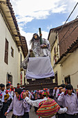 Cusco, Peru - January 2, 2012: A group of men is carrying a litter with a Jesus statue on a street festival.