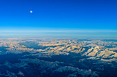 The moon rises over the Swiss mountains, aerial view