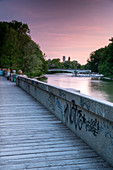 Pedestrian path between Isar and Auer Mühlbach south of Maximiliansbrücke with a view of the cable bridge and the tower of the Müller'schen Volksbad, Munich, Bavaria, Germany