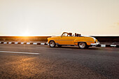 Vintage car drives along the Malecon in the sunset, Havana, Cuba