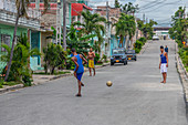 Young people play soccer on the streets of Santiago de Cuba, Cuba