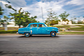 Blue classic car drives through the streets of Santiago de Cuba, Cuba