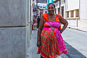 Cuban woman in colorful dress stands on the street, Camagüey, Cuba