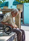 Elderly Cuban man sitting on a park bench, Camagüey, Cuba