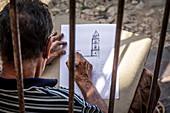Artist draws bell tower in Trinidad, Cuba