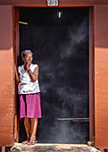 Woman coughs because it smokes in the kitchen, Trinidad, Cuba