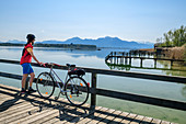 Woman cycling stands on jetty and looks at Chiemsee, Hochgern in the background, Chiemseeradweg, Chiemgau, Upper Bavaria, Bavaria, Germany