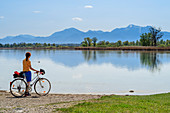 Woman cycling stands on the shore and looks at Chiemsee, Hochfelln and Hochgern in the background, Chiemseeradweg, Chiemgau, Upper Bavaria, Bavaria, Germany