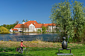 Woman cycling in front of Klostersee and Kloster Seeon, Kloster Seeon, Benediktradweg, Chiemgau, Upper Bavaria, Bavaria, Germany