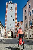 Woman cycling through city gate of Mühldorf, Mühldorf, Benediktradweg, Upper Bavaria, Bavaria, Germany