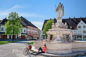 Woman cycling sits at fountain and takes a break, Altötting, Benediktradweg, Upper Bavaria, Bavaria, Germany