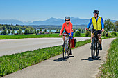 Woman and man cycling, Tachinger See and Chiemgau Alps in the background, Tachinger See, Benediktradweg, Upper Bavaria, Bavaria, Germany
