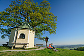 Woman and man cycling while taking break at chapel, Samerberg, Chiemgau, Chiemgau Alps, Upper Bavaria, Bavaria, Germany