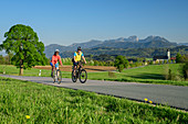 Woman and man cycling, Wilparting Church and Mangfall Mountains in the background, Irschenberg, Upper Bavaria, Bavaria, Germany