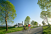 Woman and man cycling, Wilparting church in the background, Irschenberg, Upper Bavaria, Bavaria, Germany