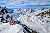Woman on ski tour looks over edge into the depths, Plereskopf, Matscher Valley, Ötztal Alps, South Tyrol, Italy